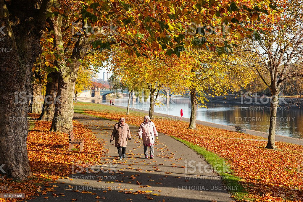Couple walk by the River Trent during Autumn. stock photo