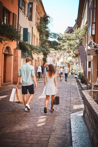ehepaar spaziert mit einkaufstaschen die promenade hinunter - sommerferien baden württemberg stock-fotos und bilder