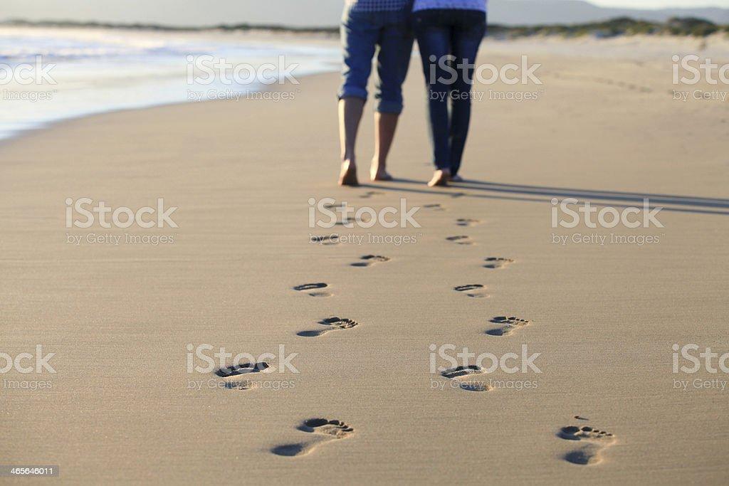 Couple walking across beach shoreline leaving footprints stock photo