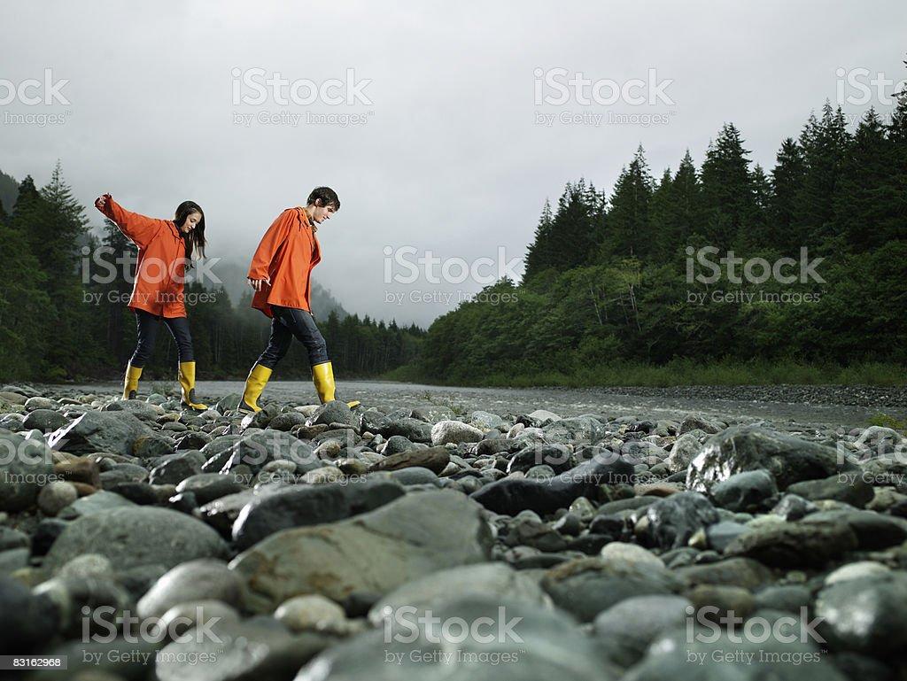 Couple walking across rocks of river bank. royaltyfri bildbanksbilder