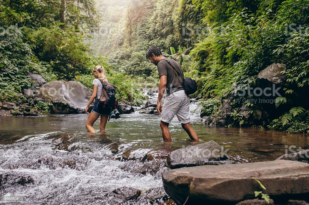 Couple walking across the stream. stock photo