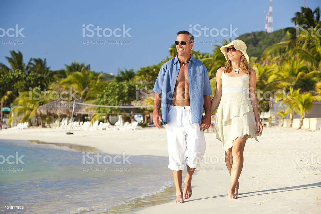 Couple Walking Along Beach stock photo
