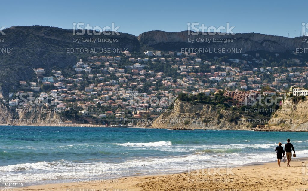 Couple walking along Calpe beach in Southern Spain. stock photo