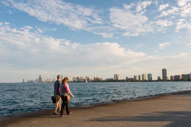 paar entlang lake michigan mit skyline von chicago in der ferne - lake michigan strände stock-fotos und bilder