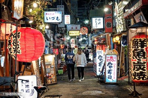 istock Couple walking along old lantern street in Namba, Japan. 1164830530
