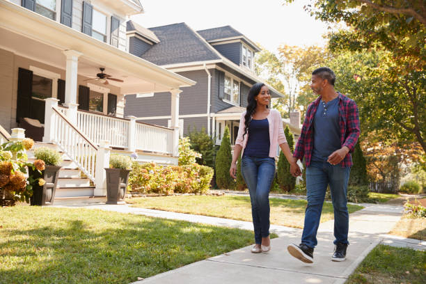 couple walking along suburban street holding hands - suburban street stock photos and pictures