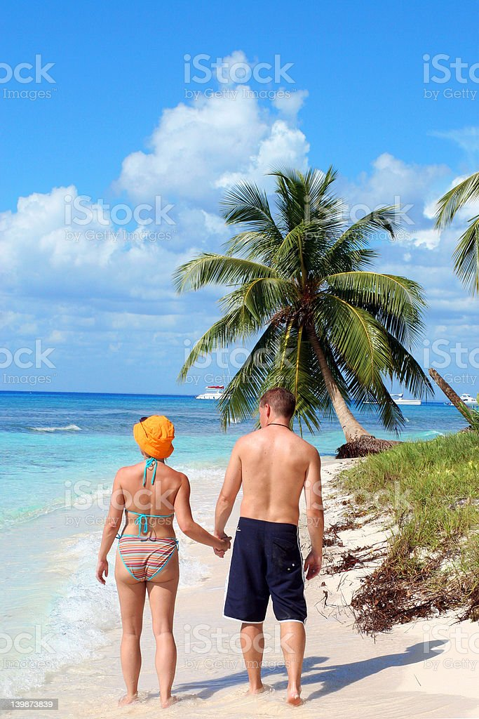 Couple walking along tropical beach royalty-free stock photo