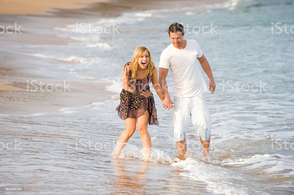 Couple walking and holding hands on the beach royalty-free stock photo
