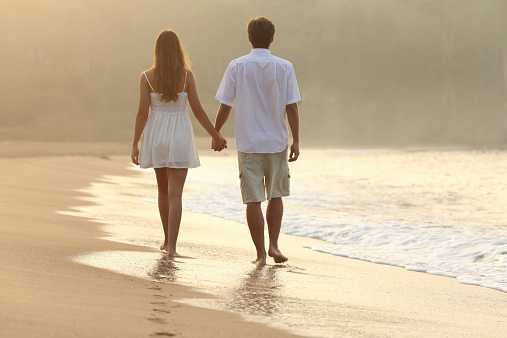 Couple walking and holding hands on the sand