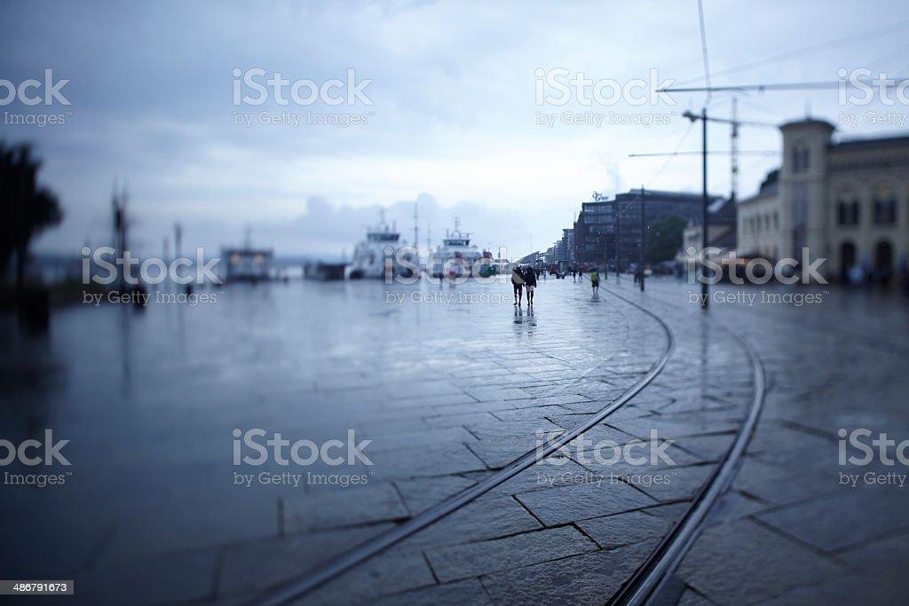 Pareja caminando en el puerto de Oslo en un día de lluvia melancólica - foto de stock