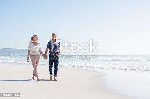 istock Couple walking at beach 530590290