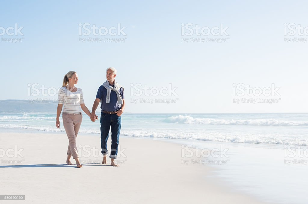 Couple walking at beach stock photo