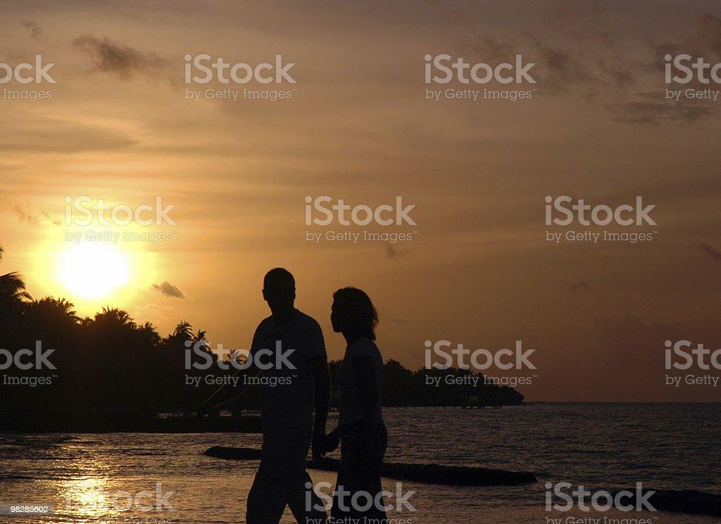 Couple walking at sunset royalty-free stock photo