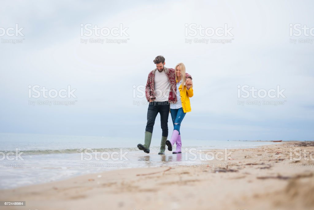 Couple walking at the beach stock photo