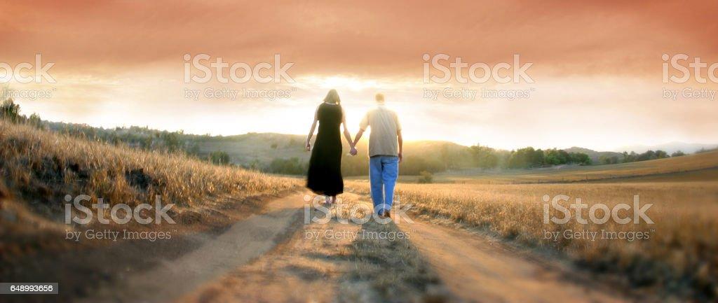 Couple Walking Away at Sunset - Stock image stock photo