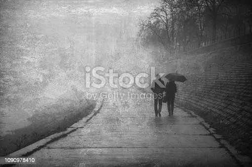 Couple walking beside the river on a misty winter day.