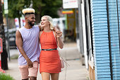 A couple walk down a city street.  The man is African American and has bleach blonde hair styled up.  He is wearing a purple sleeveless shirt and pink shorts.  The woman is caucasian and also has bleach blonde hair, she is wearing a coral colored dress and flats.  They have their arms around each other and they are laughing.