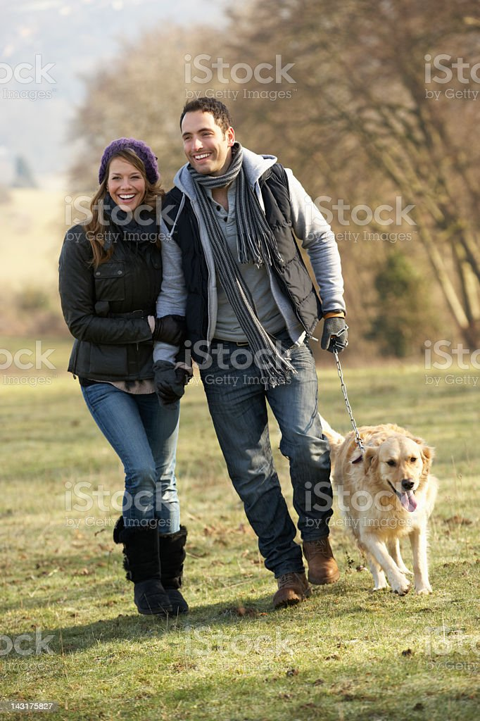 Couple walking golden retriever in the country royalty-free stock photo