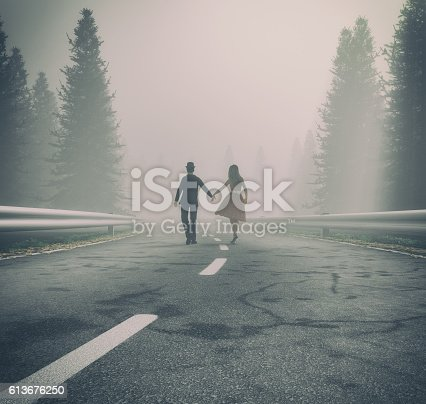 istock Couple walking hand on a forest road 613676250