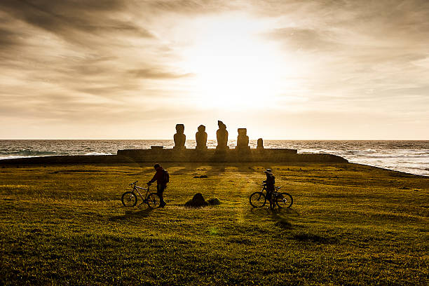Couple walking in Ahu Tahai Moai Statues at Sunset Hanga Roa, Easter Island, Chile - August 10, 2014: Passing couple with their bikes in front of Ahu Tahai Moai Statues. indo pacific ocean stock pictures, royalty-free photos & images