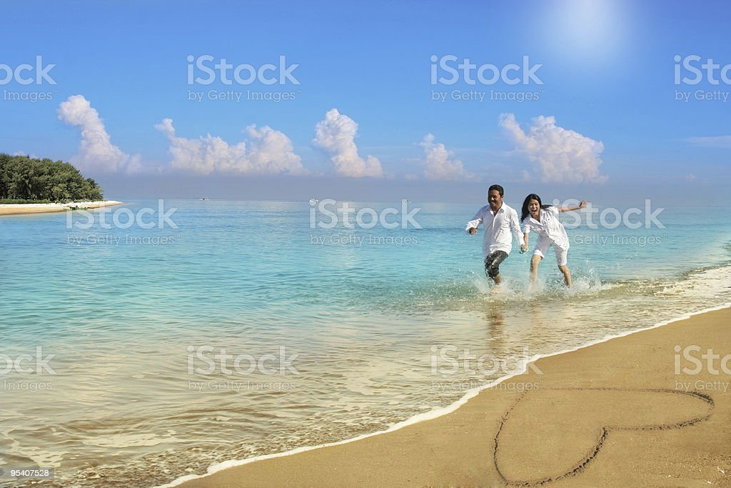 Couple walking in sea next to heart drawn in the sand stock photo