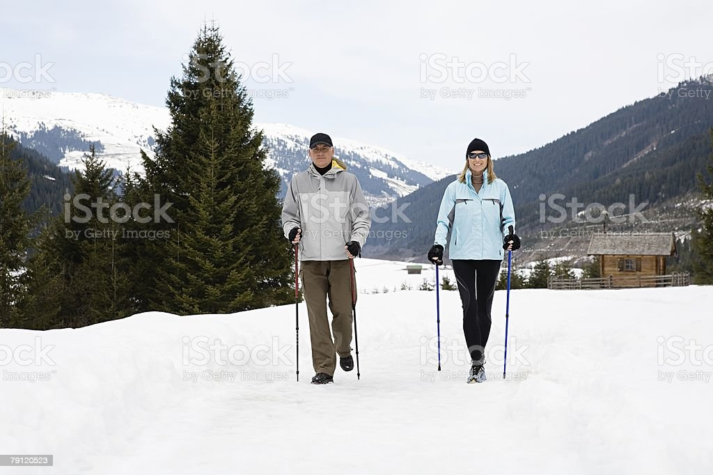 Couple walking in snow stock photo