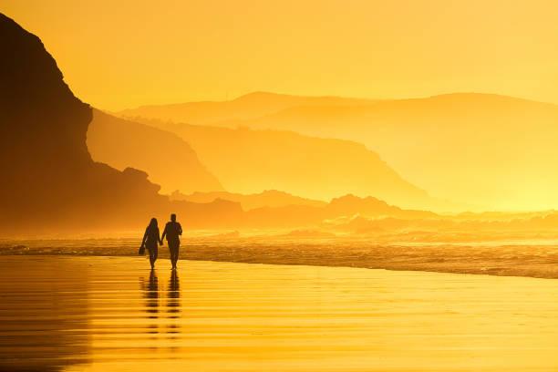pareja caminando en la playa a la puesta del sol - foto de stock