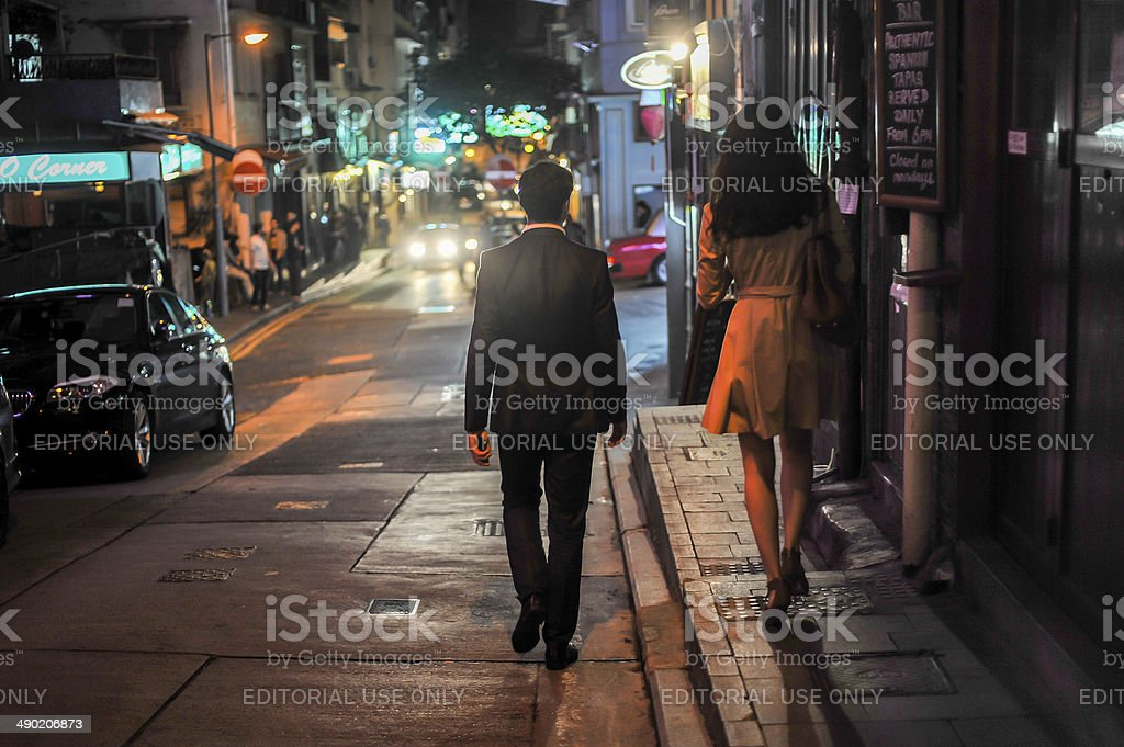 Couple walking in the street at night,Hong Kong stock photo