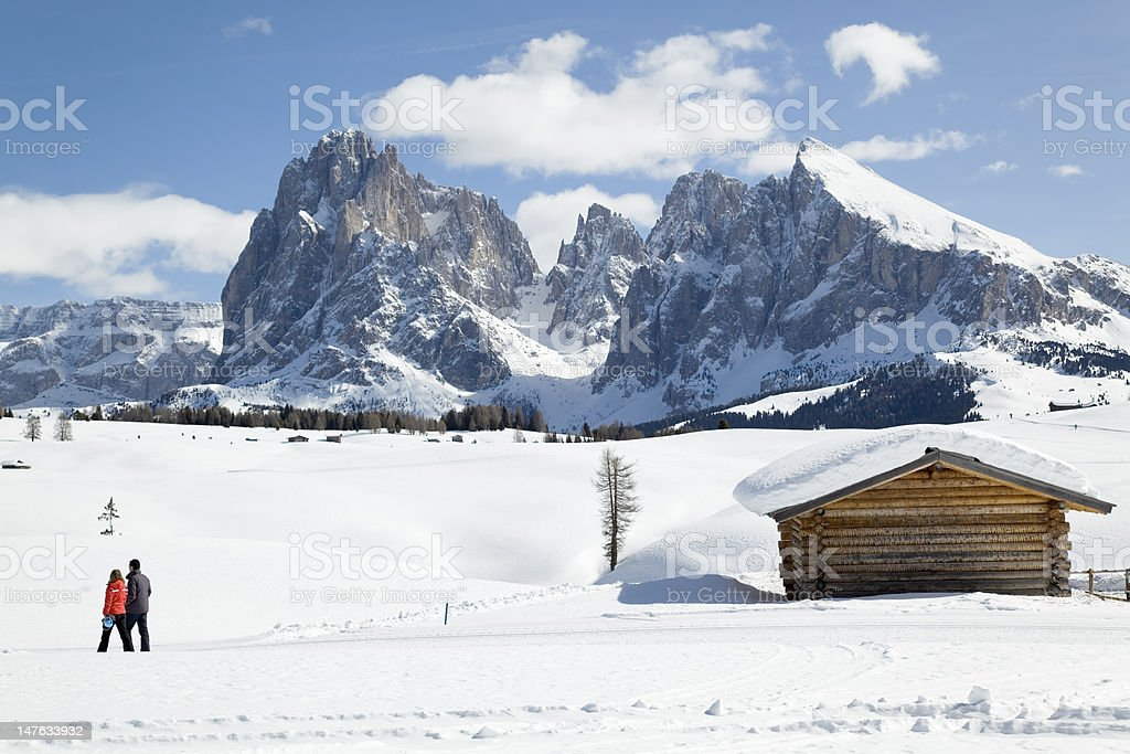 Couple walking in winter landscape with Langkofel (Dolomites, Italy) royalty-free stock photo