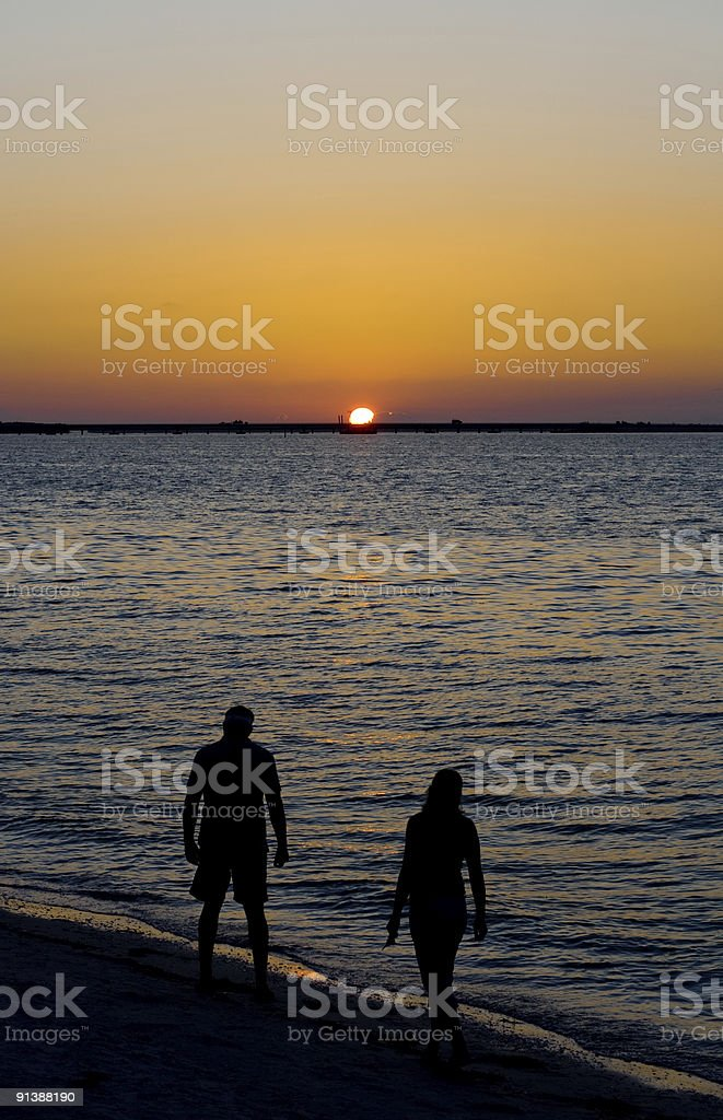 Couple Walking on Beach Admiring the Sunset royalty-free stock photo