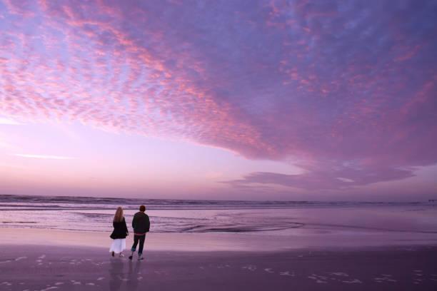 Couple walking on beach at sunrise, enjoying time together. stock photo