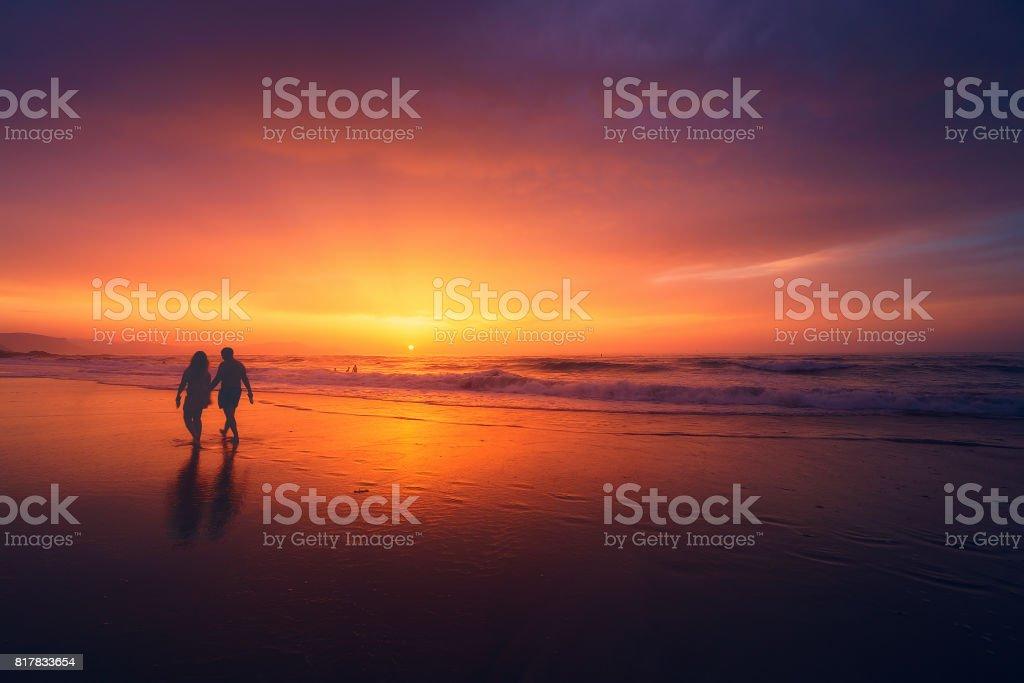 couple walking on beach at sunset stock photo