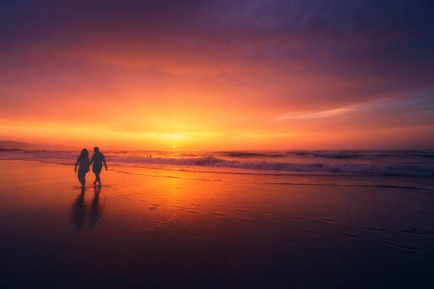 couple walking on beach at sunset stock photo