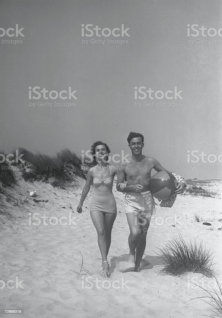 Couple walking on beach, man carrying ball, (B&W) stock photo