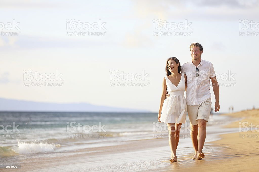 Couple walking on beach. Young happy interracial couple walking on...