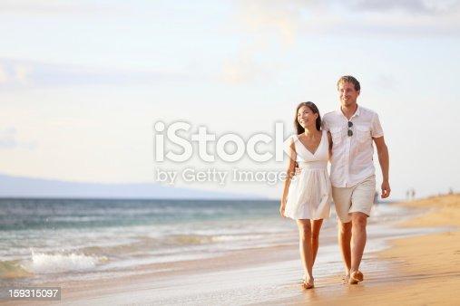 istock Couple walking on beach 159315097