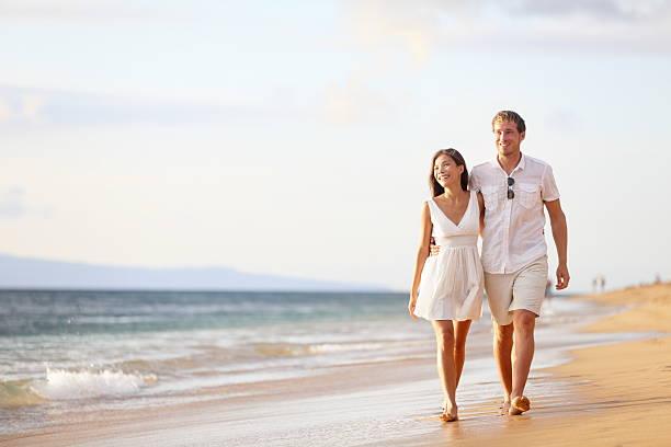 Couple walking on beach stock photo