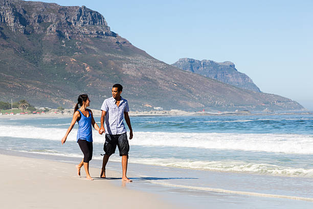 couple walking on beach - carolinemaryan stock pictures, royalty-free photos & images