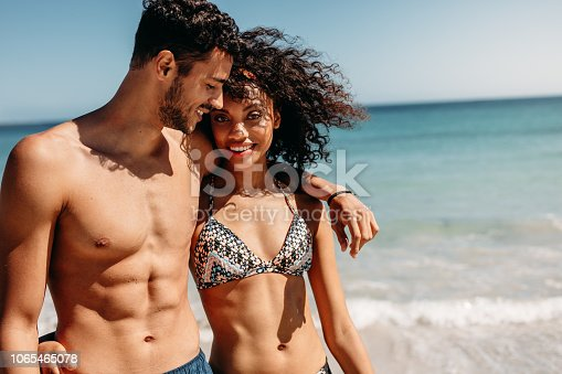 Romantic couple walking on beach together on a sunny day. Smiling man walking on beach with girlfriend putting his arm around her shoulder.