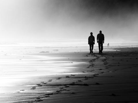 couple walking on foggy beach