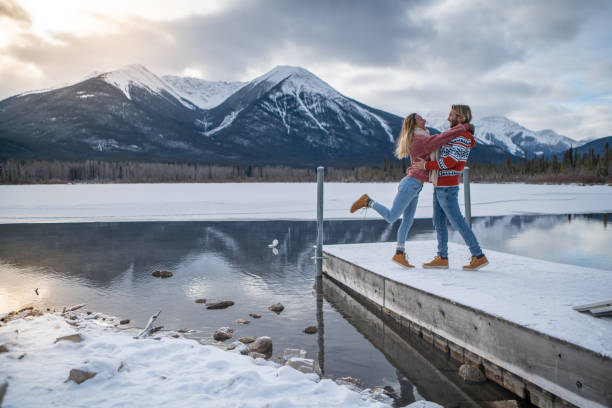 Couple walking on jetty over frozen lake in winter, Canada stock photo
