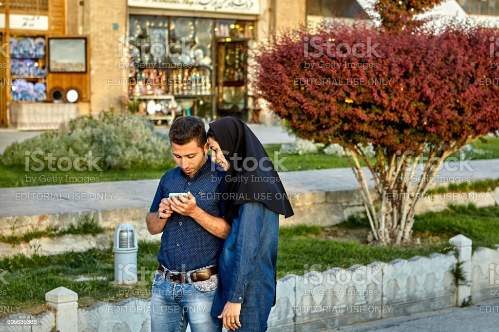 Couple walking on Naghshe Jahan square, and viewing  smartphone screen. stock photo