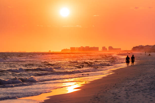 Couple walking on shore with dramatic orange red yellow sunset in Santa Rosa Beach, Florida with Pensacola coastline coast cityscape skyline in panhandle with ocean gulf mexico waves stock photo