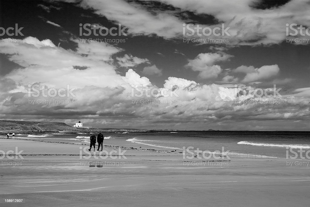 Couple walking on the beach at Bamburgh royalty-free stock photo