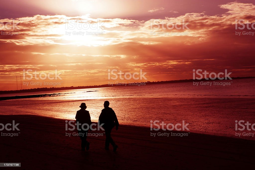 A couple walking on the beach at sunset royalty-free stock photo