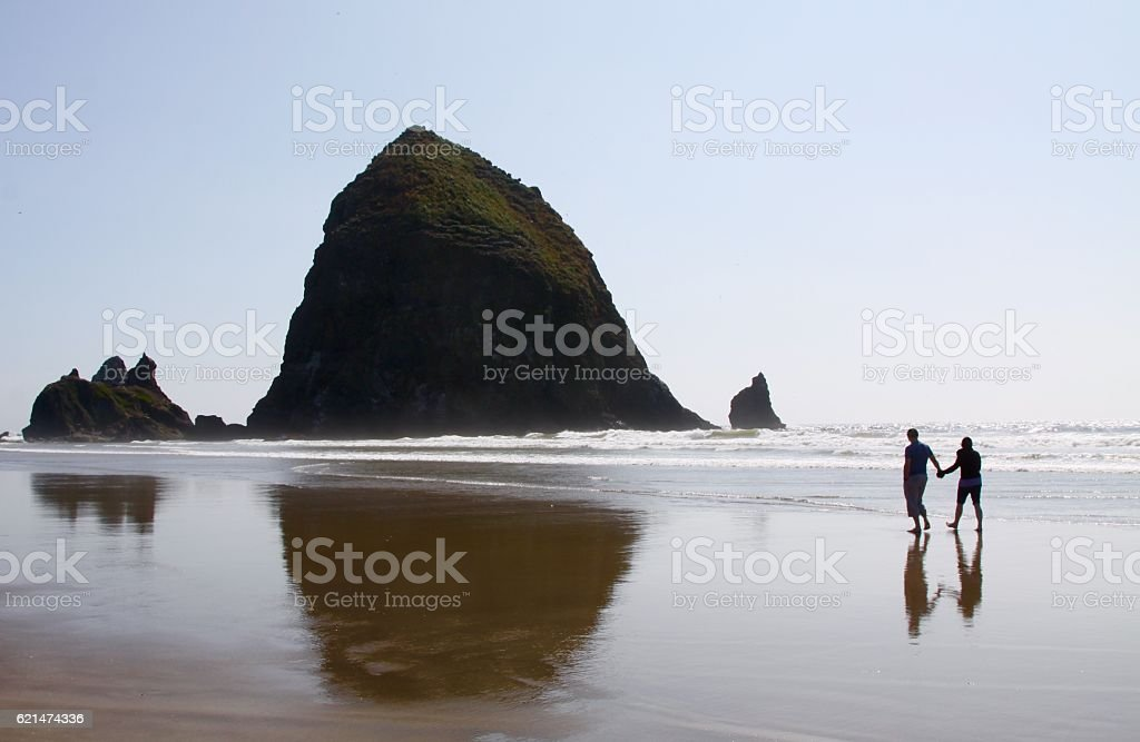 Couple Walking On The Beach Near Haystack Rock stock photo