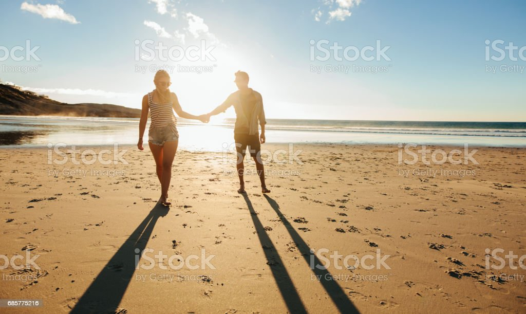 Couple walking on the beach together at sunset royalty-free stock photo