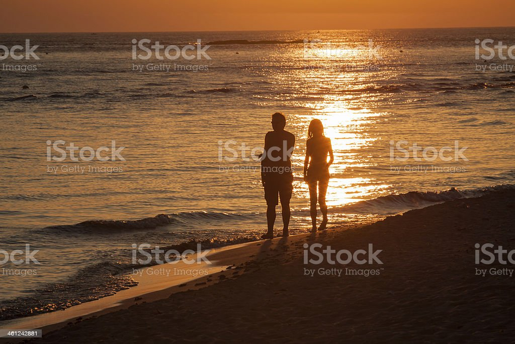 Couple walking on the seashore silouette at sunset royalty-free stock photo