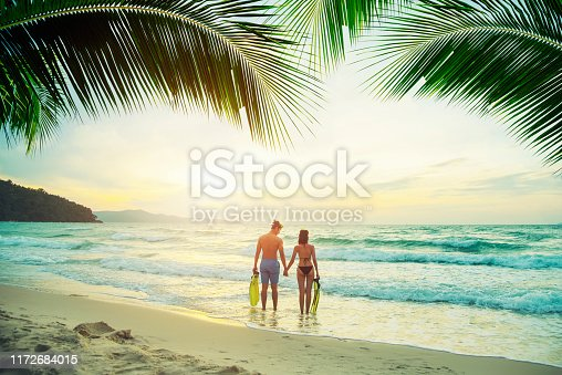 Couple walking on the tropical beach at sunset. Travel and vacation concept.