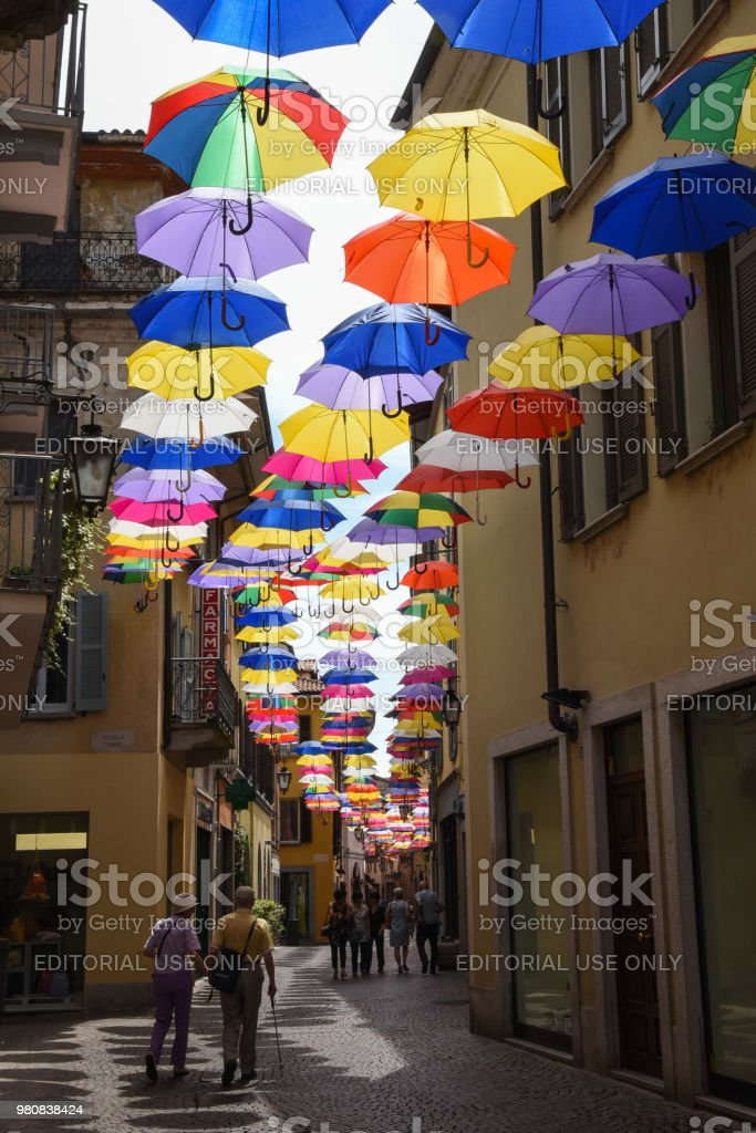 Couple walking on umbrella covered street in Italy stock photo
